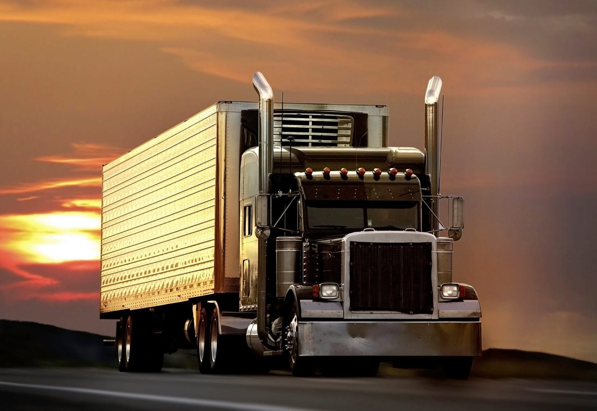 Semi-truck driving on the highway during sunset.