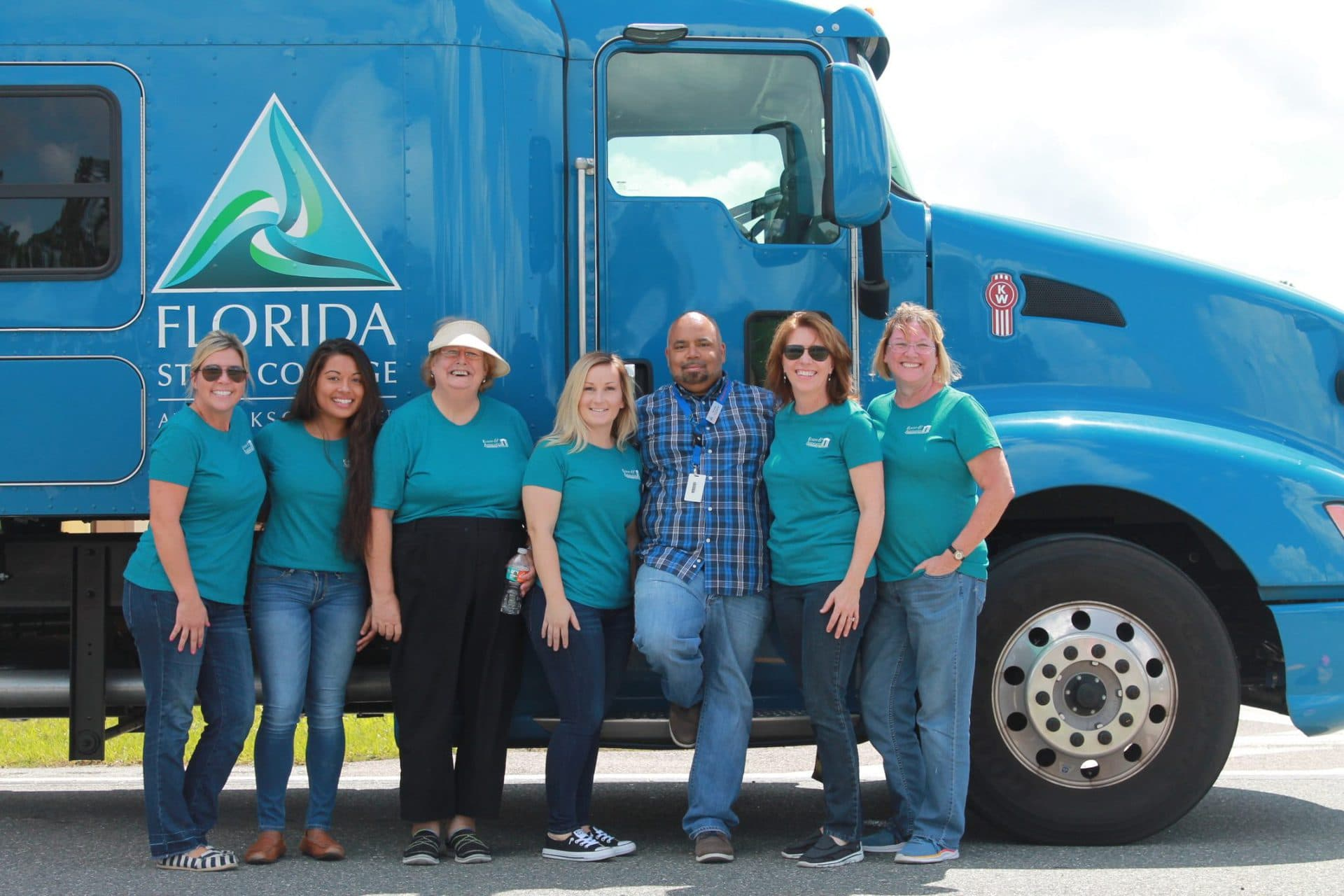 Staff standing against truck.