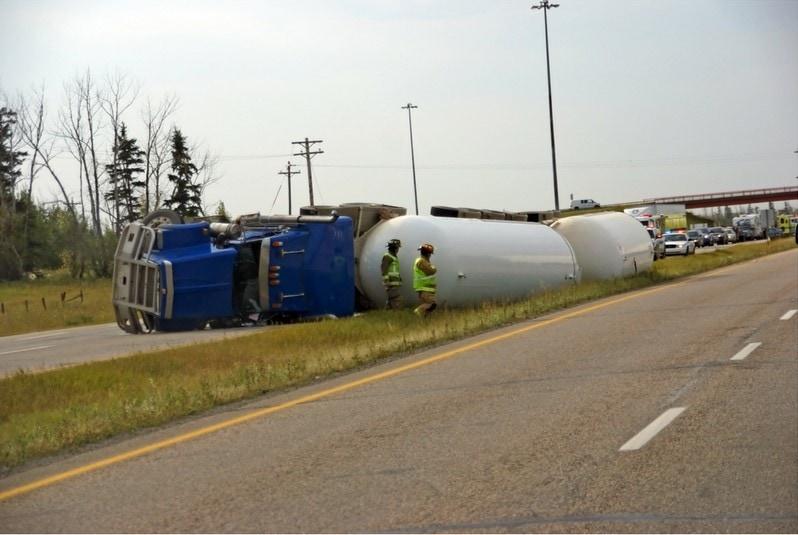 Overturned sem-truck on side of the highway.