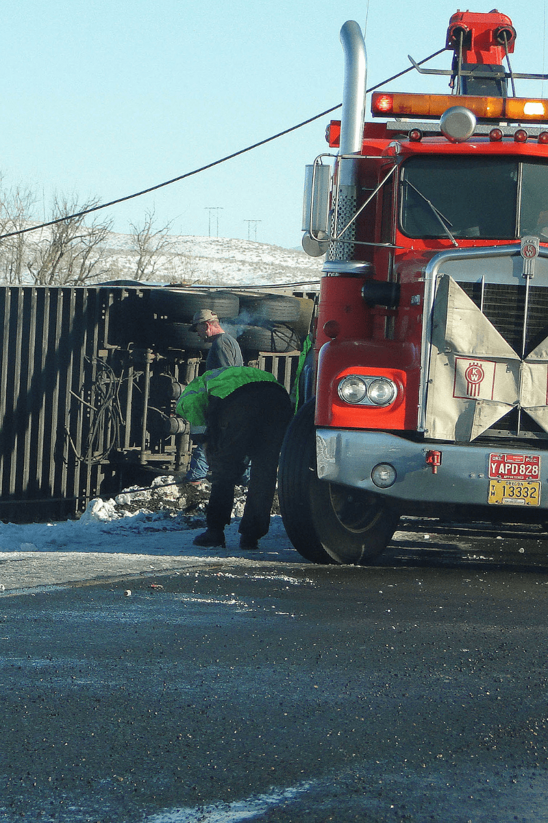 Man observing tire of semi-truck on side of the road.