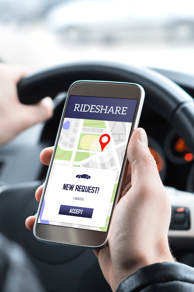 A hand holding a smart phone showing rideshare